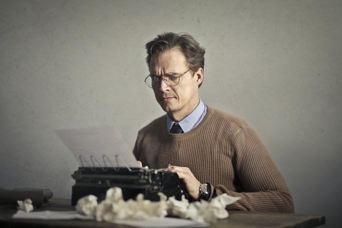Писатель работает на пишущей машинке дома