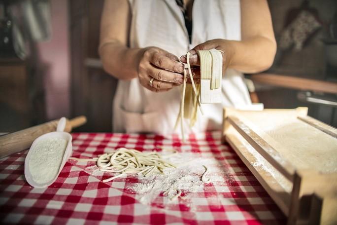 Женщина готовит лапшу на кухне