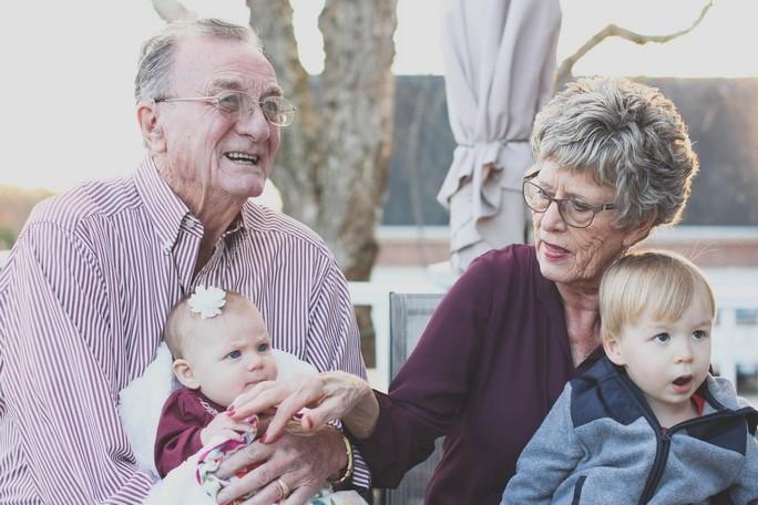 Дедушка и бабушка с детьми на коленях