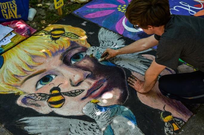 Молодой человек рисует на полу объемную картину