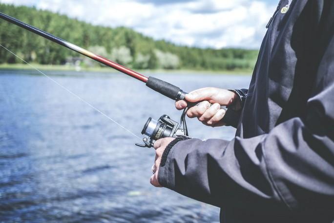 Рыбак держит в руках удочку