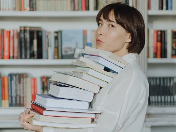 Девушка со стопкой книг в руках