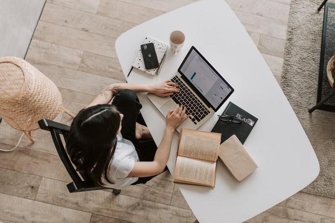 Девушка работает с книгами за ноутбуком