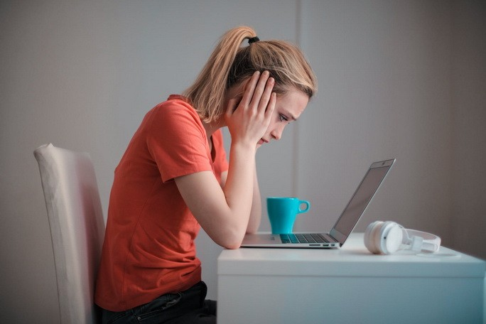 Девушка держится за голову глядя в ноутбук